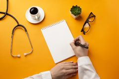 Professional doctor writing medical records in a notebook with stethoscope, coffee cup and glasses stock image