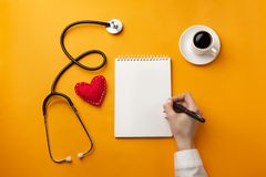 Professional doctor writing medical records in a notebook with stethoscope, coffee cup, syringe and heart stock photos