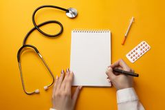 Professional doctor writing medical records in a notebook with stethoscope, syringe and pills royalty free stock image