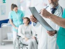 Professional doctors examining patient`s x-ray stock photos