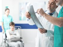 Professional doctors examining patient`s x-ray. Confident professional doctors examining a patient`s x-ray and women on wheelchair helped by a nurse on the royalty free stock photography