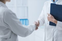 Doctors meeting in the office. Professional doctors meeting in the office and giving a handshake, cooperation and teamwork concept royalty free stock image