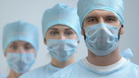 Professional doctors in uniform looking camera, qualified medical team, surgery. Stock footage stock video