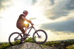Professional Down Hill Cyclist Resting with Bike on the Rock at Sunset. Extreme Sport. Stock Photo