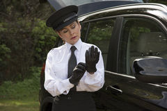 Professional driver putting on her driving gloves Stock Image