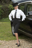 Professional driver standing with hands on hips by her car Stock Photography