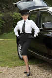 Professional driver standing with hands on hips by her car Royalty Free Stock Images