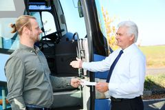 Professional driver taking ticket from passenger. Near bus royalty free stock image