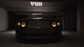 Professional driver testing new expensive car in garage, switching on headlights. Stock footage stock video