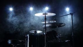 Professional drum set with chair. Black smoky background. Back light. Side view. Professional good drum set with plates, drum sticks and chair in the studio stock video footage