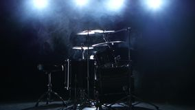 Professional drum set with chair. Black smoky background. Back light. Side view. Professional good drum set with plates, drum sticks and chair in the studio stock footage