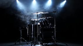 Professional drums in the studio. Black smoky background. Back light. Side view. Professional drum kit in the studio fully assembled with a chair for use by a stock video footage