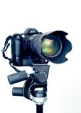 Professional DSLR camera with telephoto zoom lens on tripod
