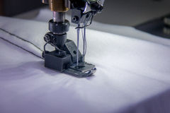 Professional dual needle sewing machine with white fabric. Dual needle sewing machine with white fabric Stock Photos