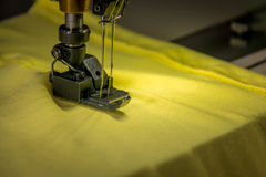 Professional dual needle sewing machine with yellow fabric. Dual needle sewing machine with yellow fabric Royalty Free Stock Photo