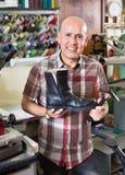Professional efficient shoemaker heeling footwear on machine Stock Photography