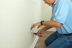 Professional electrician or experienced homeowner fixing broken. Professional electrician or experienced homeowner man using tools to disassemble an electrical Royalty Free Stock Image