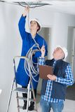 Professional electrician with pretty student on construction site. Apprentice stock photography