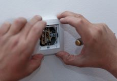 Electrician stripping the cable to connect switches and sockets. Professional electrician stripping the cable to connect switches and sockets of a residential Stock Images