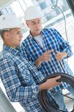 Professional electrician with student on construction site. Apprentice stock image