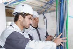 Professional electrician with student on construction site. Apprentice stock photo