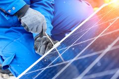 Professional electrician worker installing solar panels. Close up cropped shot of a technician worker using screwdriver installing solar panels outdoors Stock Image