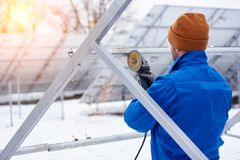 Professional electrician worker installing solar panels. Rearview shot of a professional electricity technician installing solar panels outdoors in winter Stock Photography