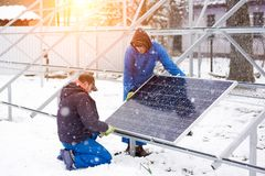 Professional electrician worker installing solar panels. Two male electricians technicians workers installing solar panels outdoors in winter alternative Royalty Free Stock Photography