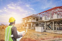Professional engineer architect worker with protective helmet. And blueprints paper at house building construction site background royalty free stock images