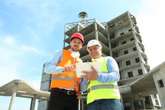 Professional engineer with tablet and foreman in equipment at construction site. Professional engineer with tablet and foreman in safety equipment at stock image