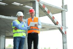 Professional engineer with tablet and foreman in safety equipment at construction site. Space for text royalty free stock photography
