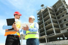 Professional engineer with tablet and foreman in safety equipment at construction site. Space for text royalty free stock images