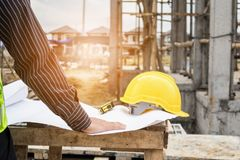 Professional engineer worker at the house building construction. Young business man professional engineer worker at the house building construction site with stock photos