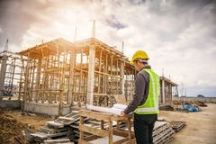 Professional engineer worker at the house building construction. Young business man professional engineer worker at the house building construction site with Stock Images