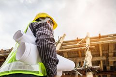Professional engineer worker at the house building construction. Young professional engineer worker in protective helmet and blueprints paper on hand working on Stock Photography