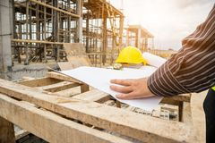 Professional engineer worker at the house building site. Young business man professional engineer worker at the house building construction site with blueprint royalty free stock image