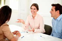 Professional executive team speaking at meeting. Portrait of professional executive team speaking at meeting while smiling and sitting on office desk Royalty Free Stock Image