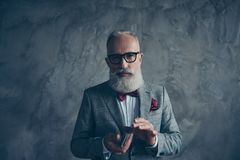 Professional, experienced, cunning, old gambler in tux with bow,. Glasses, shuffle deck of card, ready for game, standing over gray background Royalty Free Stock Photo
