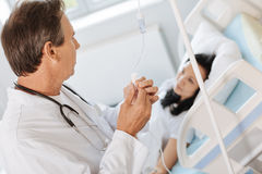 Professional experienced doctor treating his patient. My job. Professional experienced male doctor setting up the IV line and looking at his patient while Royalty Free Stock Photo