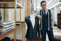 Atelier studio. Professional experienced tailor standing at mannequin with jack in his atelier studio royalty free stock photo