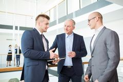 Professional Explaining Project To Colleagues On Digital Tablet. Male professional explaining project to colleagues on digital tablet in office stock photography
