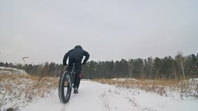 Professional extreme sportsman biker riding fat bike in outdoor. Close-up view of rear wheel. Cyclist ride in winter stock video footage
