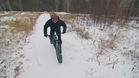 Professional extreme sportsman biker riding fat bike in outdoor. Cyclist ride in winter snow forest. Man does trial stock video footage
