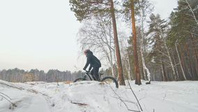 Professional extreme sportsman biker riding fat bike in outdoors. Cyclist ride in winter in snow field, forest. Man does stock video