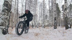 Professional extreme sportsman biker riding a fat bike in outdoors. Cyclist ride in the winter snow forest. Man does. Professional extreme sportsman biker riding stock video footage