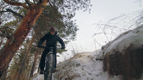 Professional extreme sportsman biker riding fat bike in outdoors. Style downhill. Cyclist ride in winter in snow