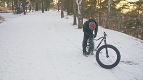 Professional extreme sportsman biker sit a fat bike in outdoor. Cyclist recline in the winter snow forest. Man walk with