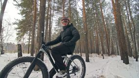Professional extreme sportsman biker sit a fat bike in outdoor. Cyclist recline in the winter snow forest. Man walk with stock video