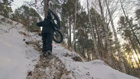 Professional extreme sportsman biker to bear fat bike to up mountain in outdoor. Cyclist walk in winter snow forest. Man