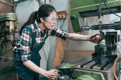 Professional factory employee wearing goggles. Beauty professional factory female employee wearing goggles protect eyes and using industrial machine to milling stock photos